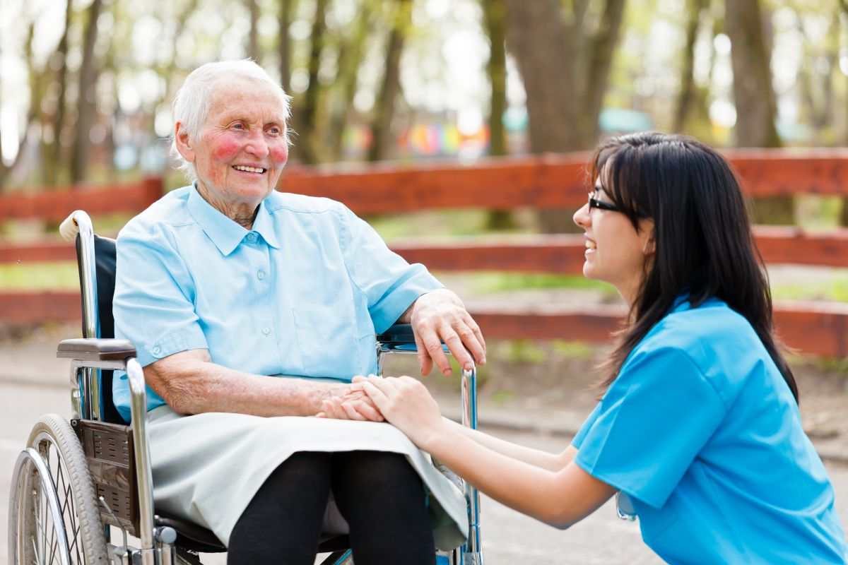 Kind nurse holding elderly lady's hand while chatting with her.
