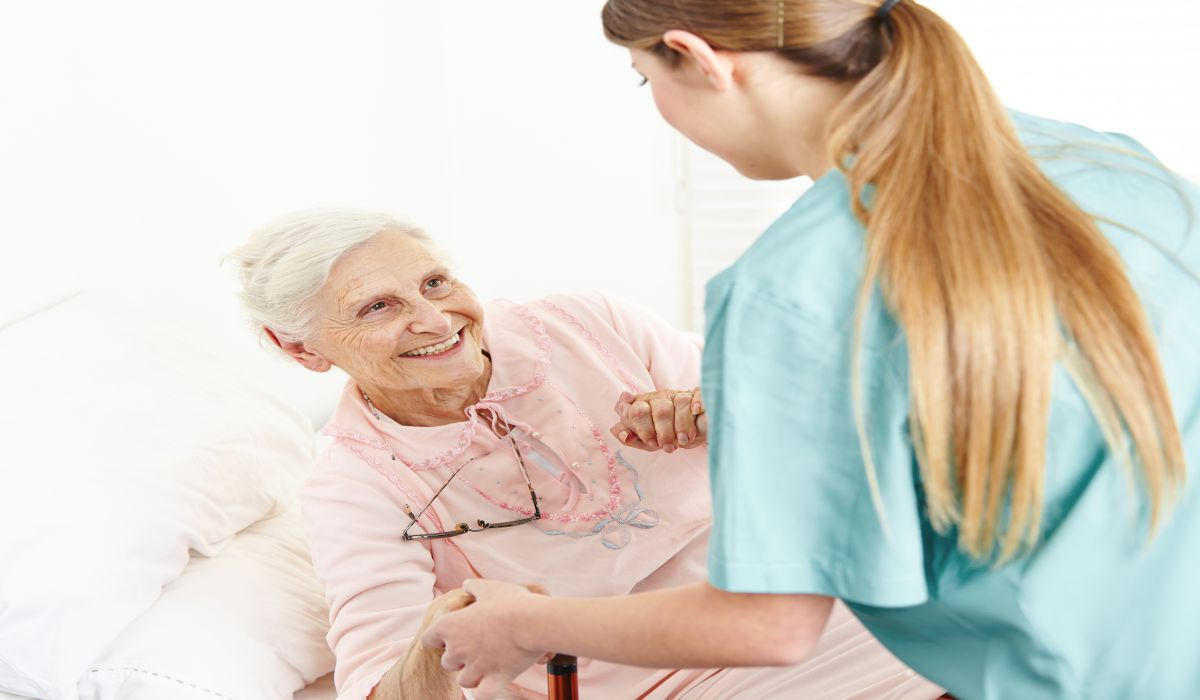 Nurse at extended home care helping smiling senior woman out of bed